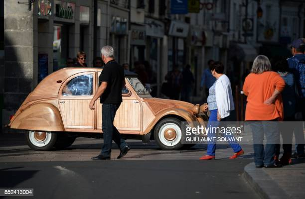People watch the wooden 2CV Citroen car made by French cabinetmaker Michel Robillard in the streets of Loches Central France on September 23 2017 A...