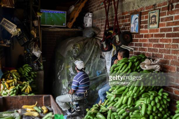 People watch the World Cup match between Colombia and Senegal on TV at a popular market in Cali Colombia on June 28 2018 Colombia beat Senegal 10 to...