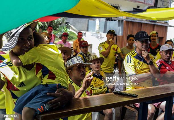 People watch the World Cup match between Colombia and Senegal on TV at the Comuna Popular 1 in Medellin Colombia on June 28 2018 Colombia beat...