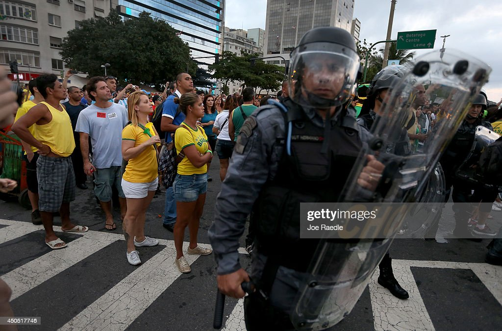 People watch the World Cup match on giant screens setup at the FIFA fan fest from behind riot police as anti-World Cup protesters pass by on Copacabana beach on June 12, 2014 in Rio de Janeiro, Brazil. Brazil defeated Croatia 3-1 in the first match of 2014 FIFA World Cup today.