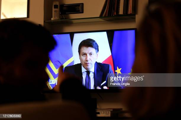 People watch tv as Italian Prime Minister Giuseppe Conte holds his speech on the new economic measures due to Coronavirus emergency on March 14 2020...