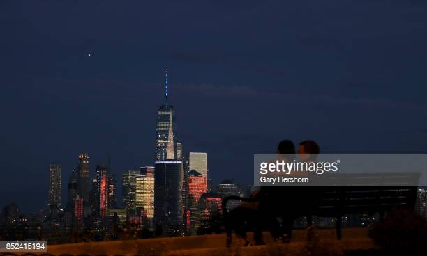 People watch twilight fall on lower Manhattan and One World Trade Center on the autumn equinox in New York City on September 22 as seen from Jersey...