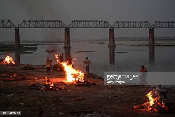 People watch unclaimed bodies burn on funeral pyres at a mass crematorium site on the banks of the Ganges river on May 05, 2021 in Allahabad, India....