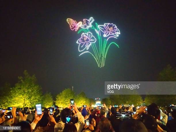 People watch unmanned aerial vehicles performance during the 10th China Flower Expo with the theme of 'Blossoming Chinese dream' on Chongming Island...