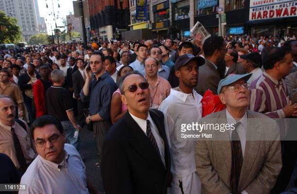 People watch World Trade Center burn September 11, 2001 after two hijacked airplanes slammed into the twin towers in New York City.