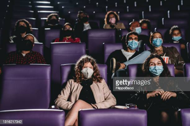 people watching a movie in a cinema during covid-19 coronavirus pandemic - film industry stock pictures, royalty-free photos & images