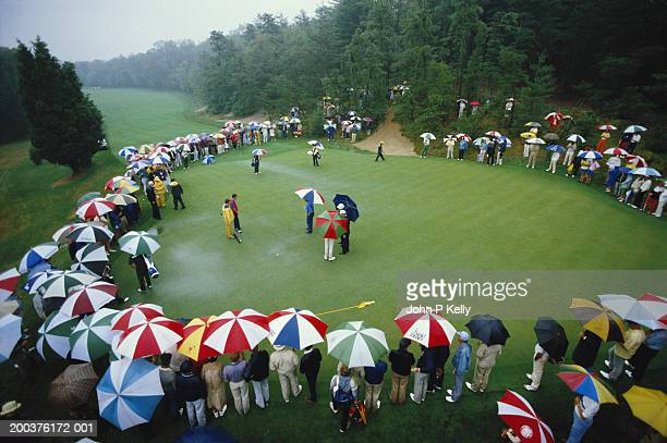 People watching amateur golf tournament in rain, elevated view