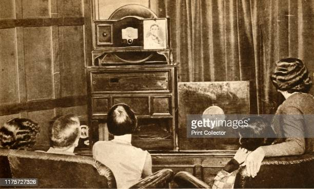 People watching an early television broadcast, circa 1930, . 'Television! By the genius of James L. Baird, sight as well as sound was successfully...