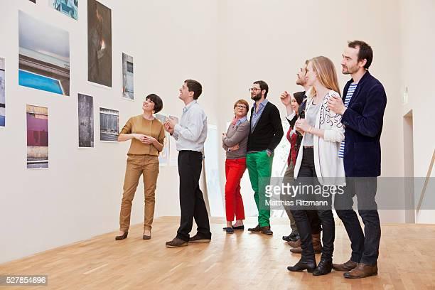 people watching exhibition of photos - 数人 ストックフォトと画像
