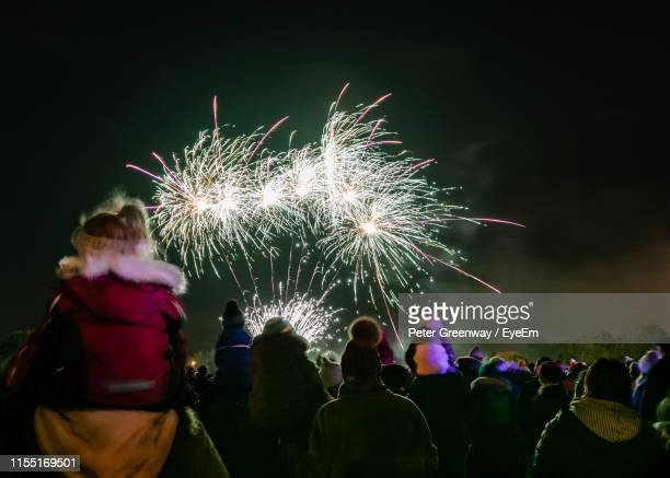 people watching firework display at night - bicester village stock pictures, royalty-free photos & images