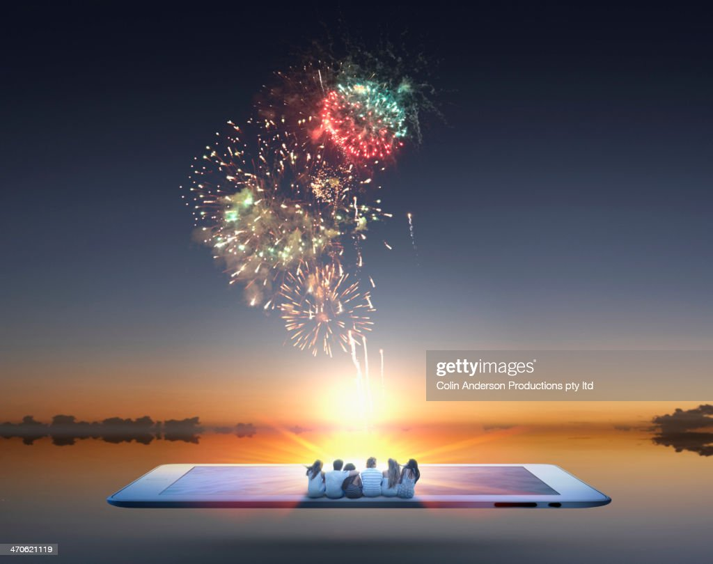 People watching fireworks erupt from digital tablet : Stock Photo