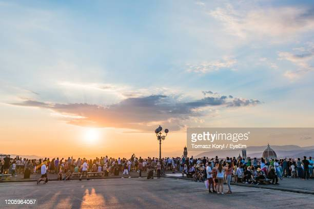 people watching florence panorama during summer sunset from piazzale michelangelo florence, italy - golden hour stock pictures, royalty-free photos & images