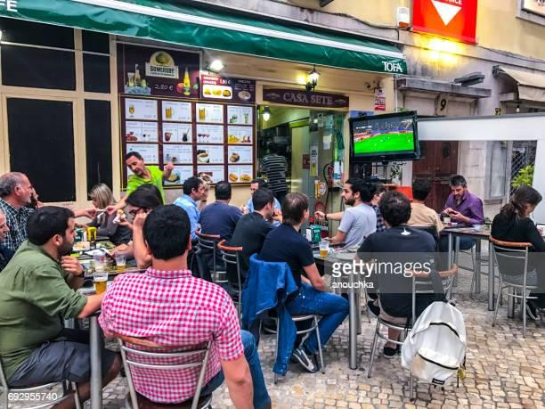 gente viendo fútbol en la tv grande fuera café calle en lisboa. - programa de televisión fotografías e imágenes de stock