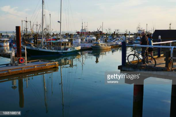 People Watching Harbor View with Fishing Boats at Steveston Fisherman's Wharf in Richmond BC Canada