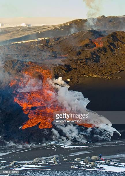 people watching lava flowing from iceland volcano - fimmvorduhals volcano stockfoto's en -beelden
