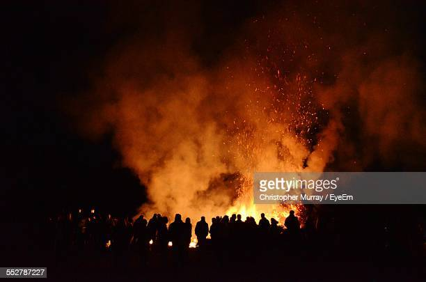 people watching lit bonfire at night during easter - osterfeuer stock-fotos und bilder