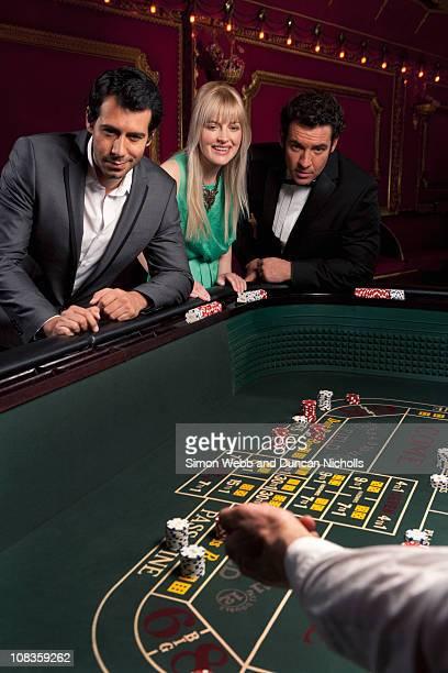 People watching man throwing dice at craps table
