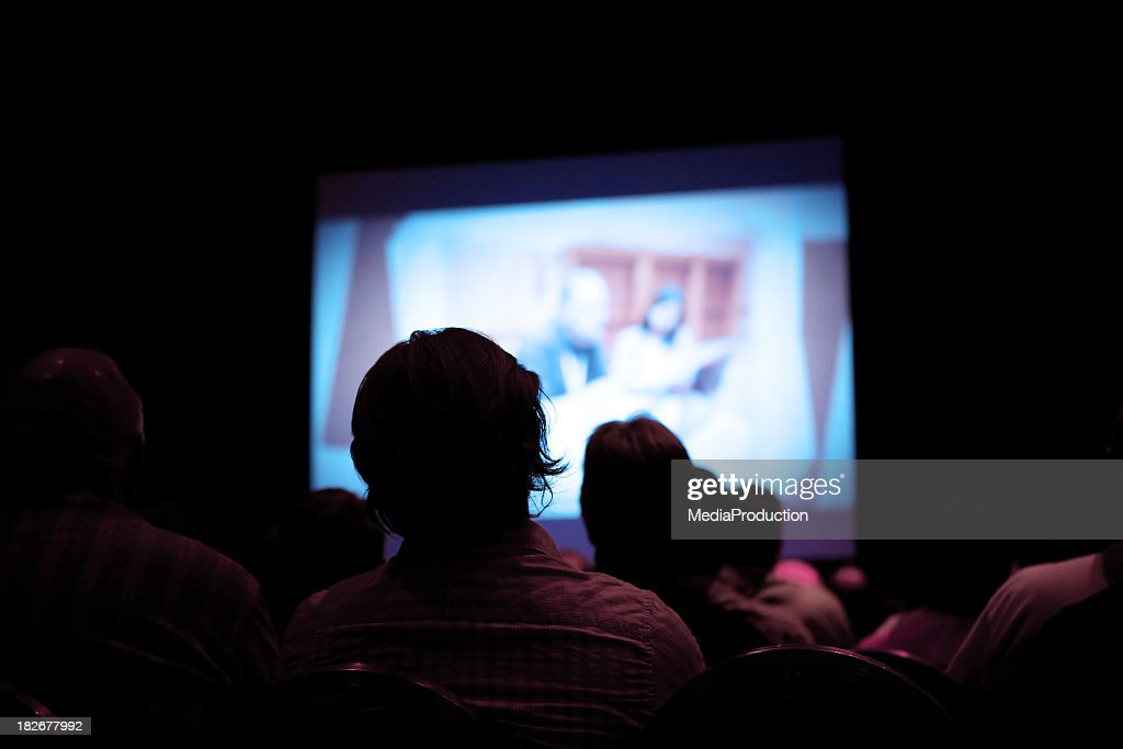 People watching movie in dark cinema : Stock Photo