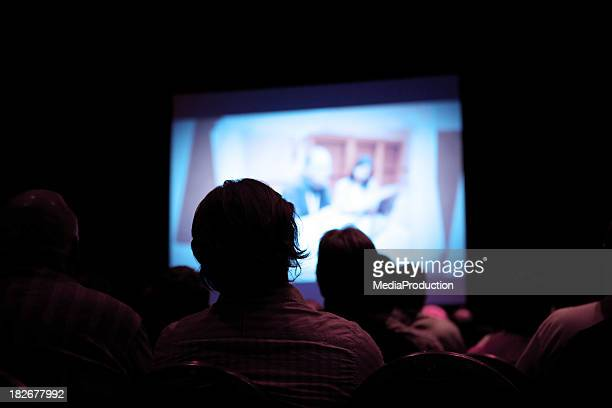 People watching movie in dark cinema