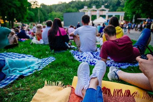 people watching movie in open air cinema in city park 984761374