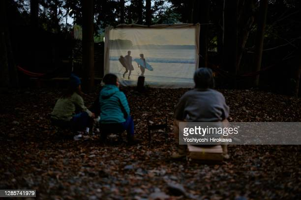 people watching outdoor movies in front of wooden camp hut - film and television screening stock pictures, royalty-free photos & images