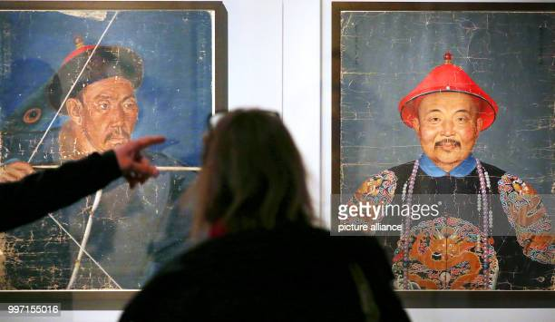 People watching portrait paintings from China depicting Moncortu shooting an arrow and Dawaci in the Kulturforum at the Matthaikirchplatz in Berlin...