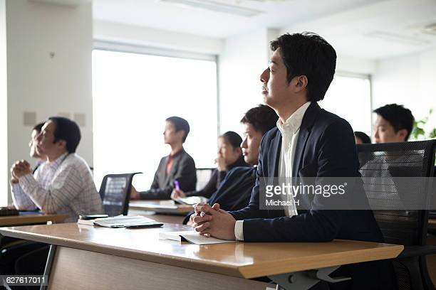 people watching presentation in conference room - 大人のみ ストックフォトと画像