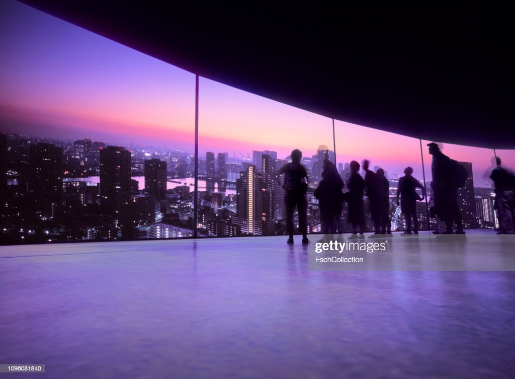 People watching projection of the Tokyo skyline on a large screen : Stock Photo