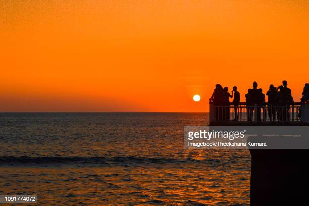 people watching sundown at galle face beach - imagebook stock pictures, royalty-free photos & images