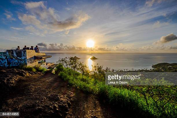 People Watching the Sunrise from an Ocean Overlook