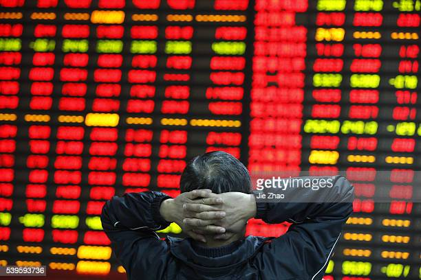 People watchs the eclectic monitor at a stock exchange in Huaibei Anhui province China on 10th April 2015 The Shanghai Composite Index climbed back...