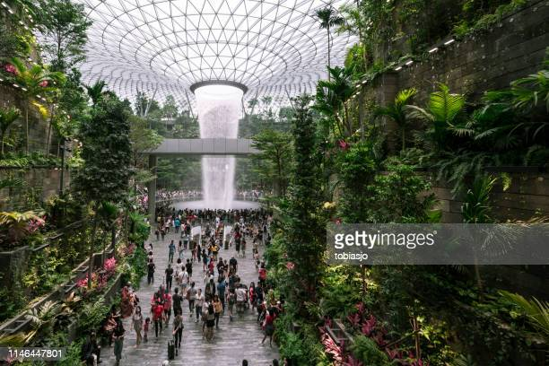 People wathcing the waterfall located inside the Jewel Changi Airport in Singapore