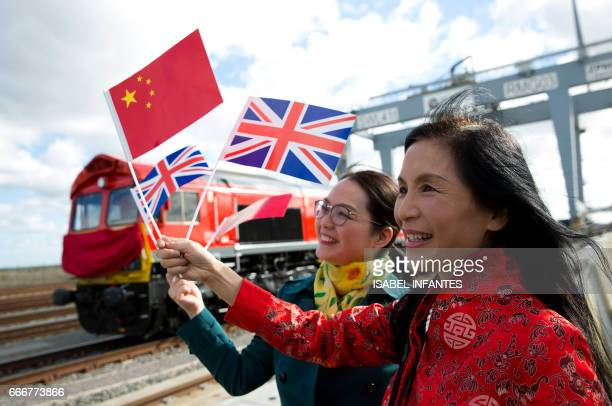 People wave a Chinese and a Union flags as they pose for photographs during a photcall to witness the departure of a freight train transporting...