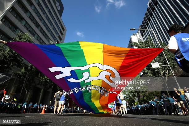People wave a rainbow pride flag during the Korea Queer Culture Festival 2018 in front of City hall on July 14 2018 in Seoul South Korea The annual...
