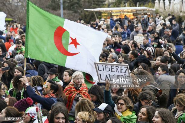 People wave Algerian national flags and hold a placard reading Free Algeria during a demonstration for equality of rights and in support of the...