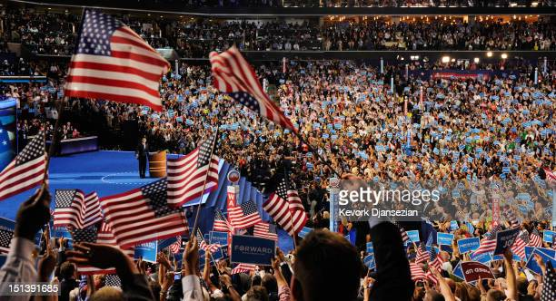 People wave American flags as Democratic presidential candidate US President Barack Obama speaks on stage to accept the nomination for president...