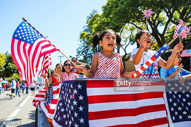 People wave American flags as they ride through 4th of July Parade in Alameda California on Monday July 4 2016 / AFP / GABRIELLE LURIE