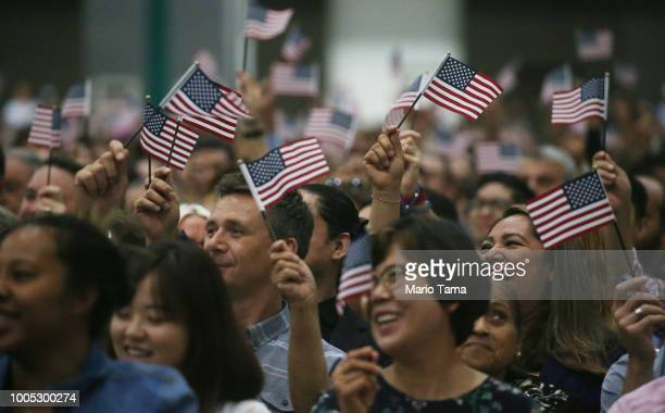 People wave American flags at a naturalization ceremony on July 25 2018 in Los Angeles California Two naturalization ceremonies held today at the Los...