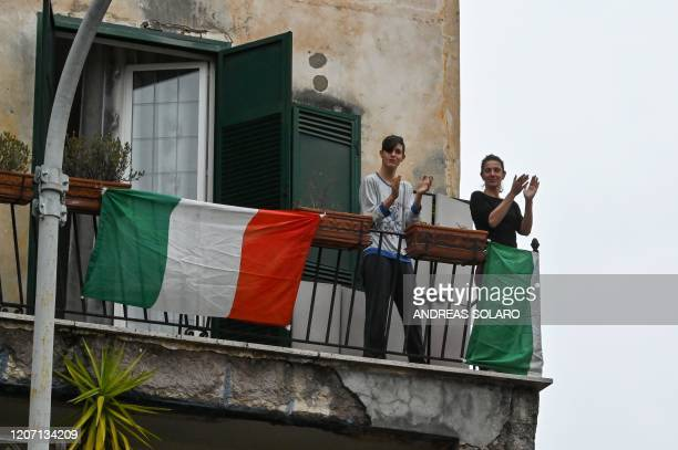 "People wave and clap their hands as part of a flash mob ""Un applauso per l'Italia"" at the Garbatella district in Rome on March 14 during the COVID-19..."