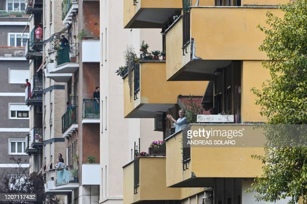 """People wave and clap their hands, during a flash mob """"Un applauso per l'Italia"""" at the Garbatella district in Rome on March 14 during the COVID-19..."""