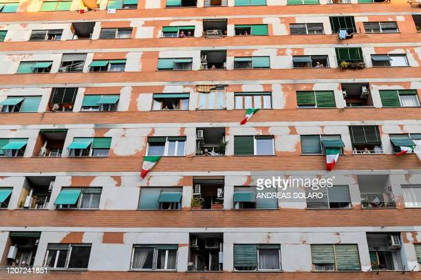 People wave and clap their hands during a flash mob Una canzone per l'Italia at Magliana district in Rome on March 15 2020 Italy reacts with the...