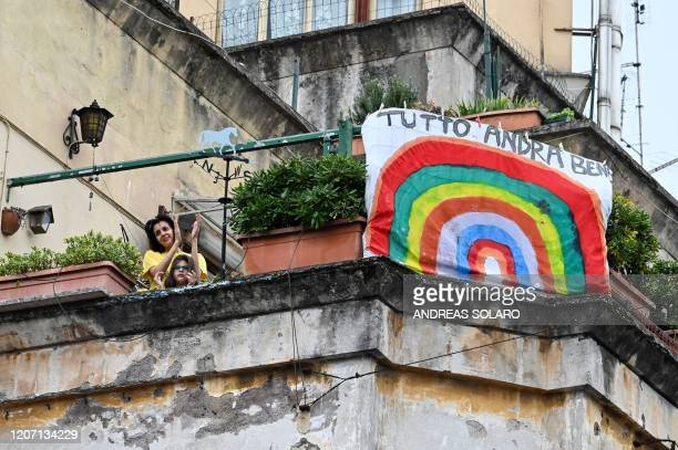 "People wave and clap their hands next to a banner reading ""hashtag #andratuttobene"" as part of a flash mob ""Un applauso per l'Italia"" at the..."
