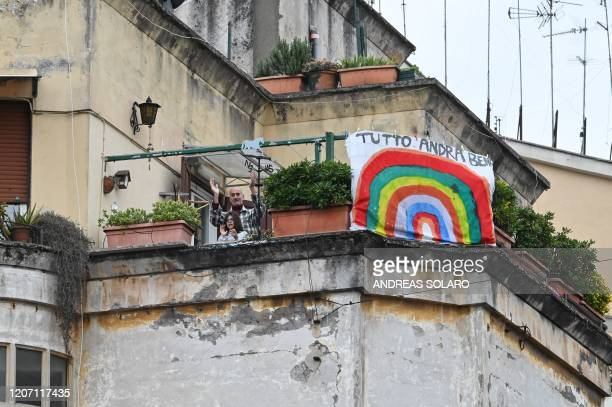 People wave and clap their hands next to a banner reading hastag #andratuttobene during a flash mob Un applauso per l'Italia at the Garbatella...