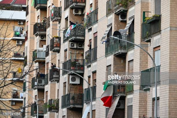 People wave and clap their hands next to a Italian flags during a flash mob Una canzone per l'Italia at Magliana district in Rome on March 15 2020...