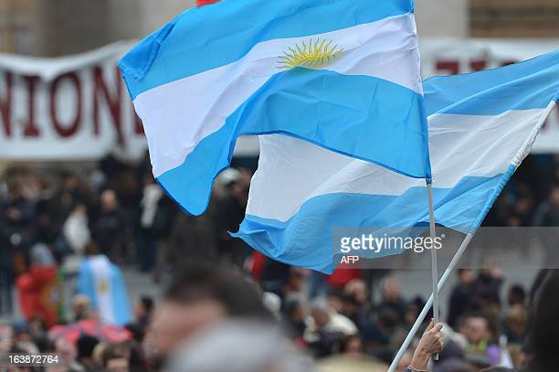 People wave Argentinian flags as they wait for pope's first Angelus prayer at St Peter's square on March 17, 2013 at the Vatican. Pope Francis begins...