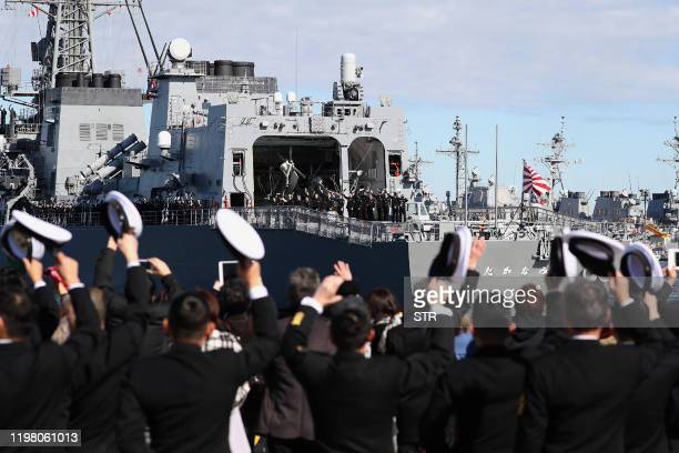 "People wave as Japan's Maritime Self-Defence Force destroyer ""Takanami"" leaves for the Middle East at Yokosuka Naval Base in Yokosuka, Kanagawa..."