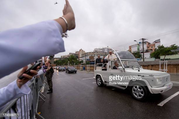 People wave as Pope Francis rides in the Popemobile back to Rio de Janeiro after celebrating Mass at the Basilica of the National Shrine of Our Lady...