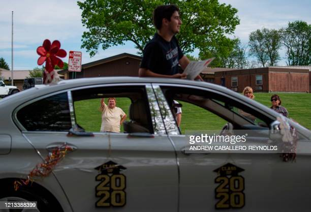 People wave as seniors from North Hagerstown High School take part in a senior ride after their prom was cancelled due to the coronavirus COVID19...