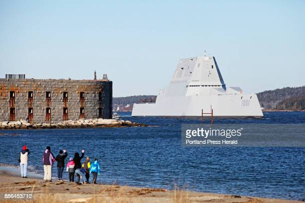 People wave as the newest Zumwaltclass stealth destroyer built by BIW passes Fort Popham as it takes a test run Monday down the Kennebec River