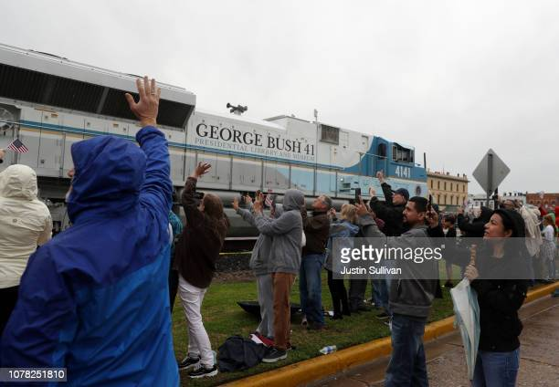 People wave at a train that is carrying the casket of former US President George HW Bush to the George HW Bush Presidential Library at Texas AM...